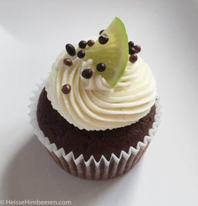 Ein Limetten Cupcake mit Frosting, Schokoperlen und einer Limettenscheibe