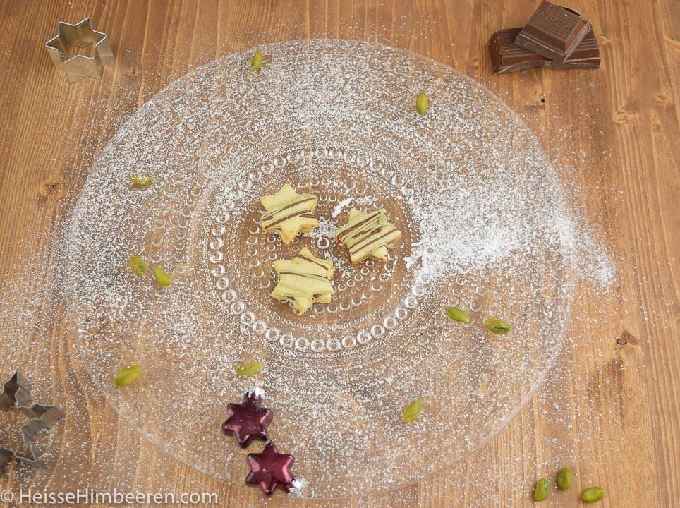 Drei Pistazien Plätzchen auf einem Teller, der mit Puderzucker bestäubt ist