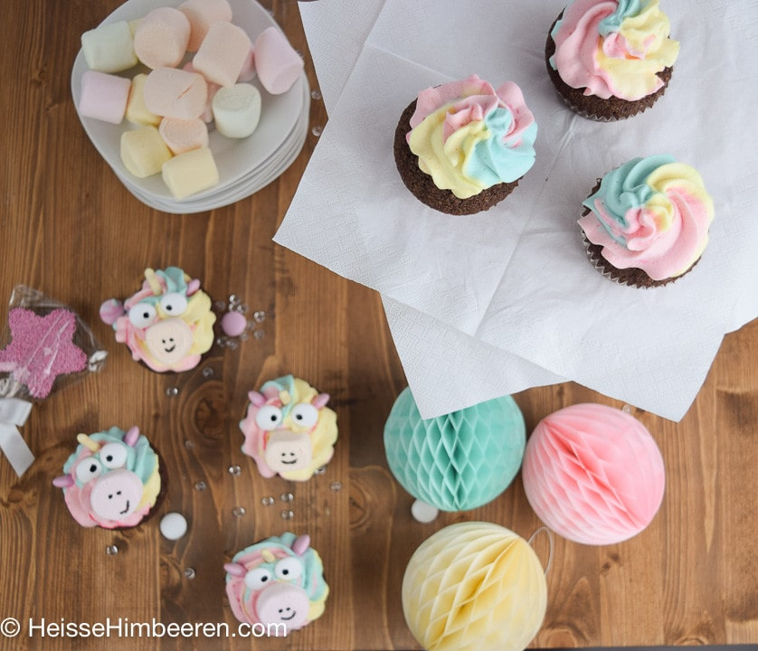 Ein Tisch voller Einhorn Muffins und bunter Dekoration