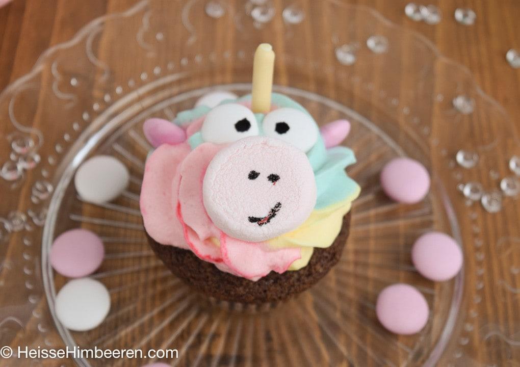 Ein Einhorn Muffins shaut direkt in die Kamera. Man erkennt das der Rüssel ein Marshmallow ist und die Augen Schokolinsen