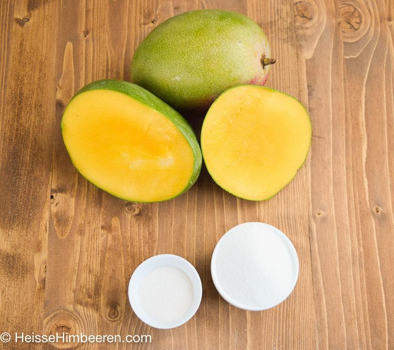 Zwei Mangos. Eine Mango ist halbiert
