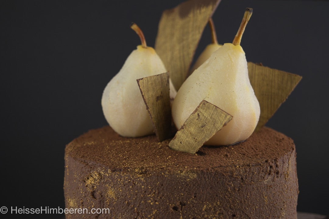 Eine Birnentorte mit Schokosahne auf der drei geschälte Birnen stehen