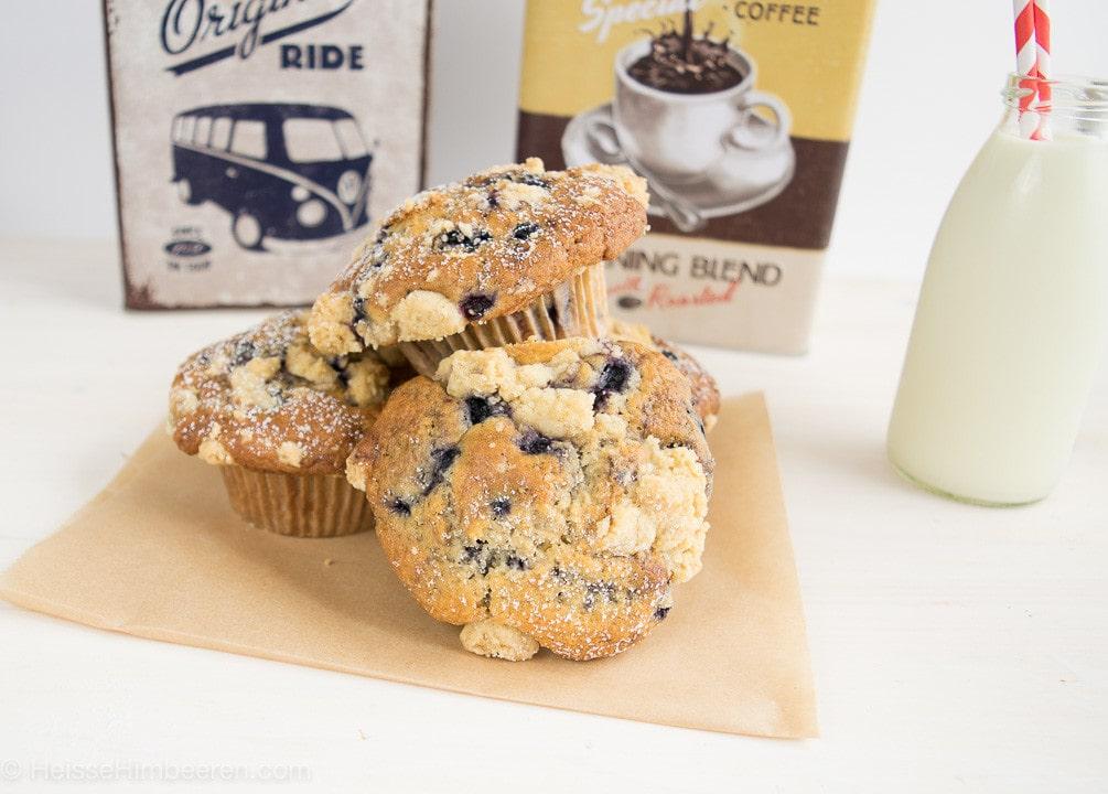 Drei Blaubeer Muffins mit Streusel auf einem Backpapier und daneben ein Glas Milch