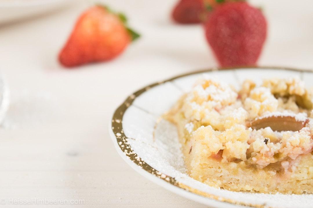 Rhabarberkuchen auf einem Teller. Im Hintergrund liegen Erdbeeren