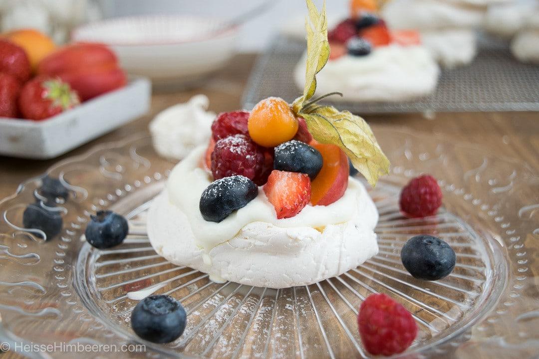 Eine Mini Pavlova mit Früchten auf einem gläsernen Teller