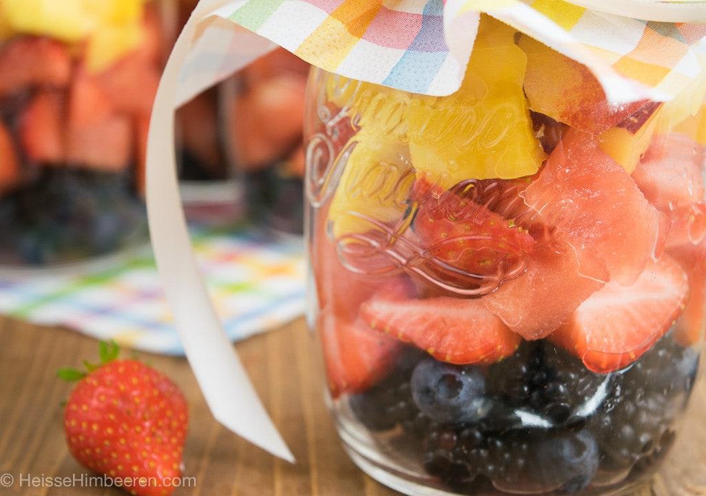 Man sieht einen Obstsalat im Glas mit Erdbeeren, Mango, Blaubeeren und Brombeeren