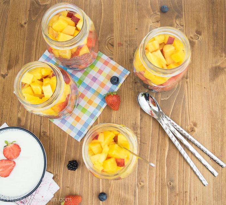 Drei Obstsalate im Glas mit drei Löffel auf einem Tisch
