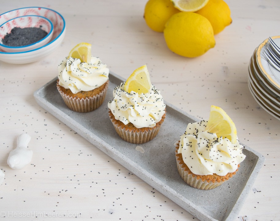 Drei Zitronen Mohn Cupcakes mit einer Creme, Mohn und Zitronenstücke