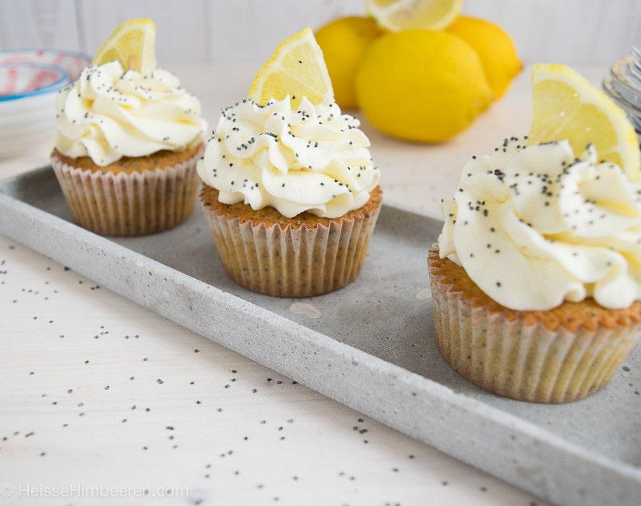 Drei Zitronen Mohn Cupcakes auf einem länglichen Teller