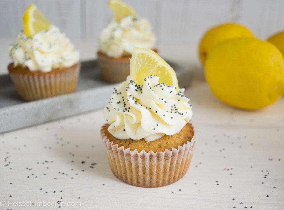Ein Zitronen Mohn Cupcakes im Fokus. Es sind Mohnsamen auf dem Cupcake zu sehen