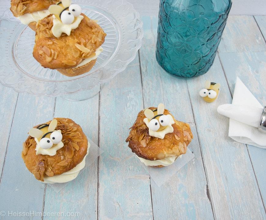 Drei Bienen Muffins auf einem hellblauen Tisch