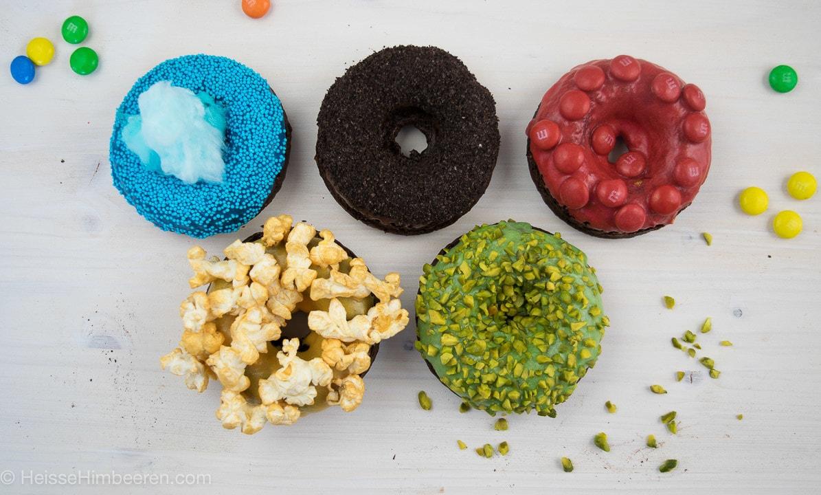 Fünf Donuts mit unterschiedlichen Donut Toppings. Von Popcorn zu Smarties bis hin zu Pistazien