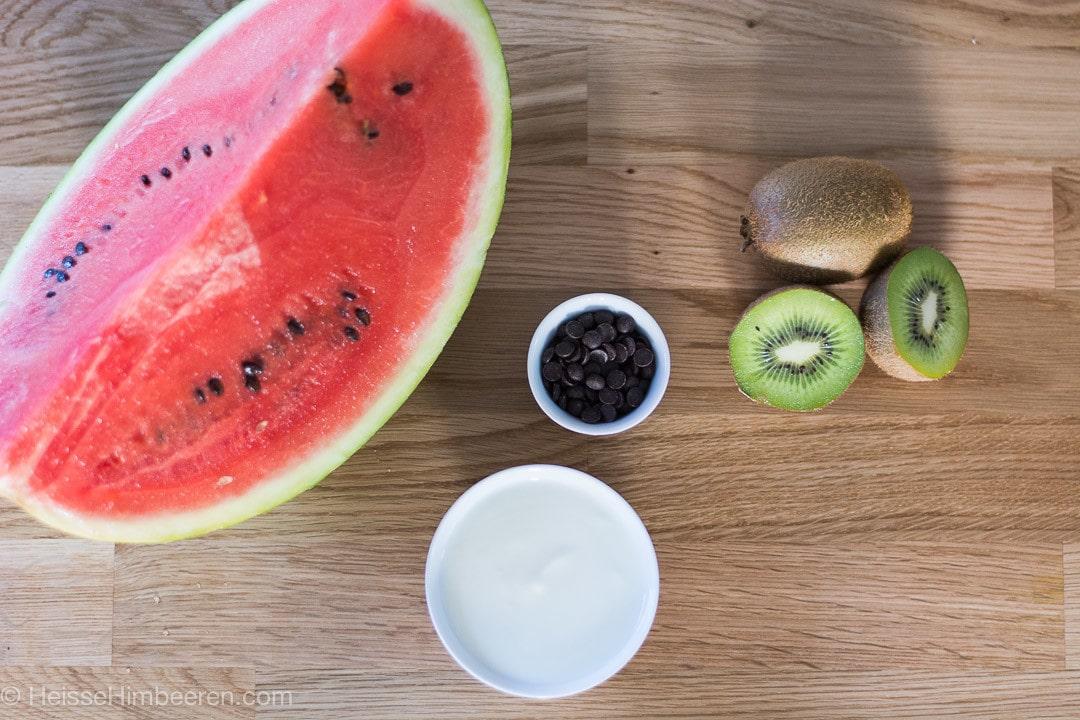 Eine viertel Wassermelone, zwei Kiwiws wobei eine halbiert ist und Schokoladenstückchen