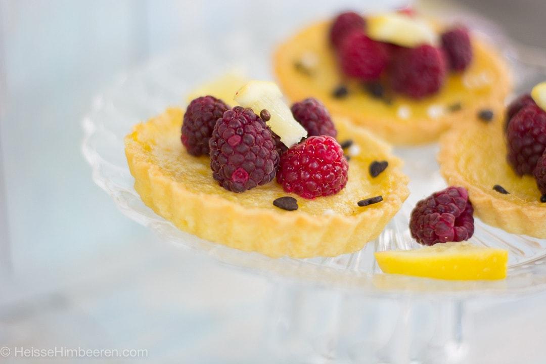 Zitronen Tartelettes mit Himbeeren auf einem dursichtigen Teller