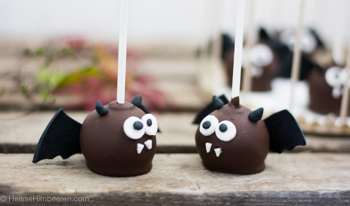 Zwei Fledermaus Cake Pops zu Halloween auf einem Holzbrett