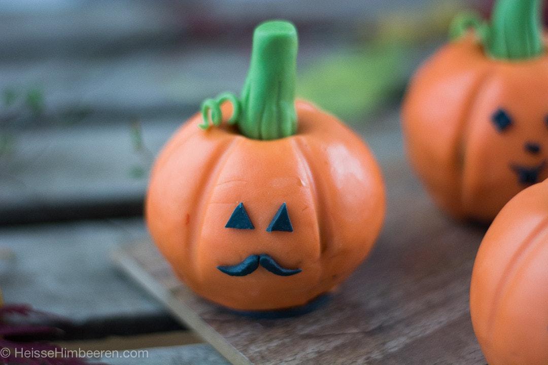 Ein Halloween Kürbis Gesicht auf einem orangen Schokokuchen Kürbis mit grünem Stangl