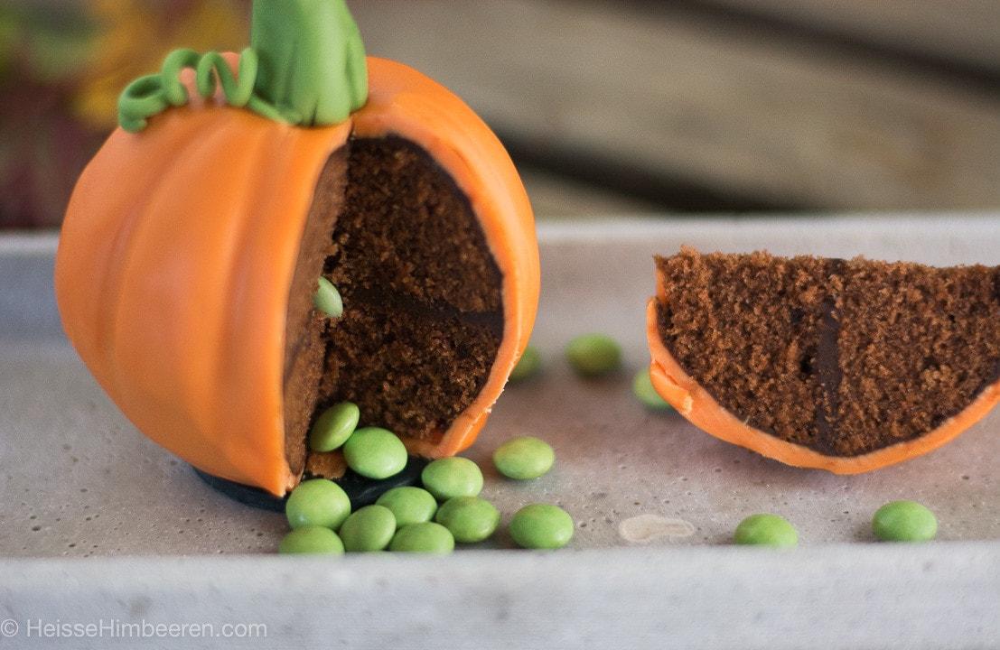 Ein angeschnittener Halloween Kürbis. Aus dem Gebäck fallen grüne Smarties