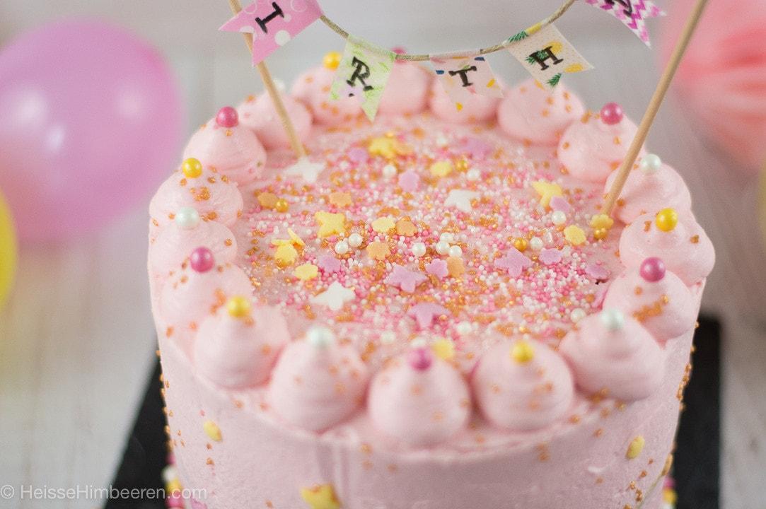 Geburtstagstorte in der Nahaufnahme. Man sieht viele bunte Streusel auf einer rosa Torte