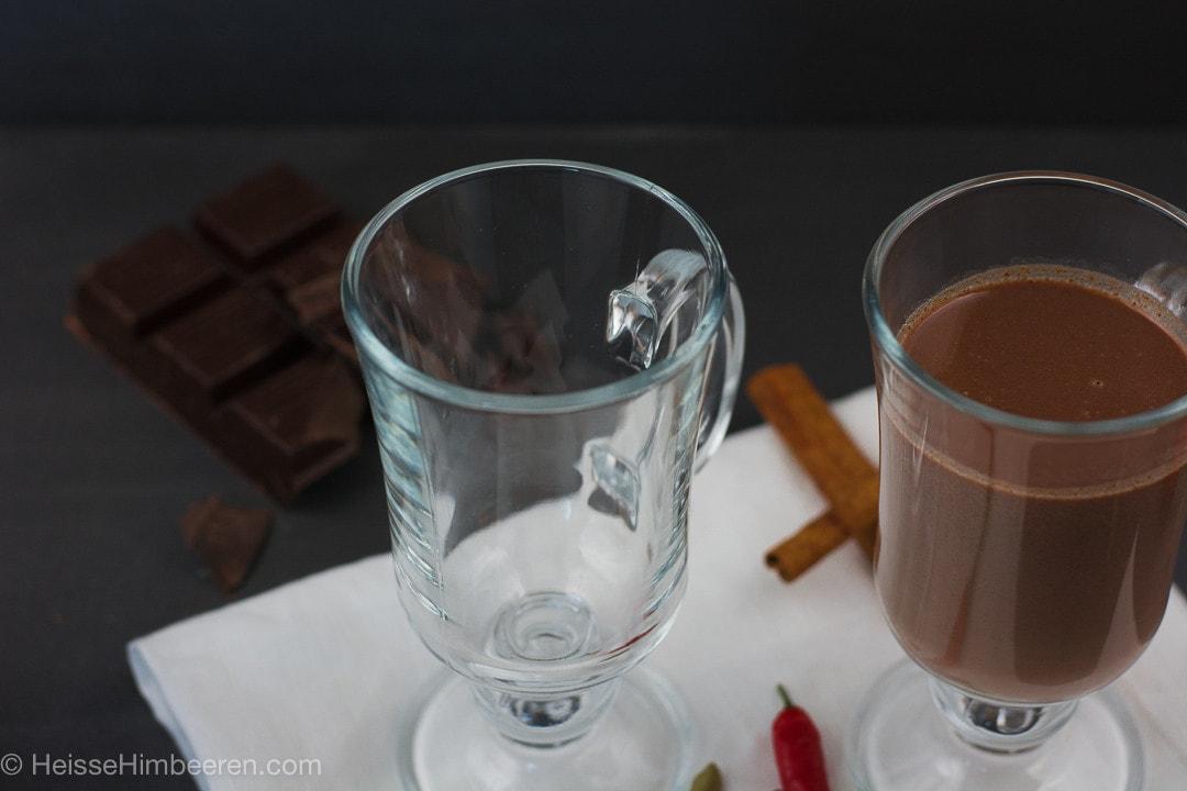 Ein leeres Glas und ein Glas mit heißer Schokolade