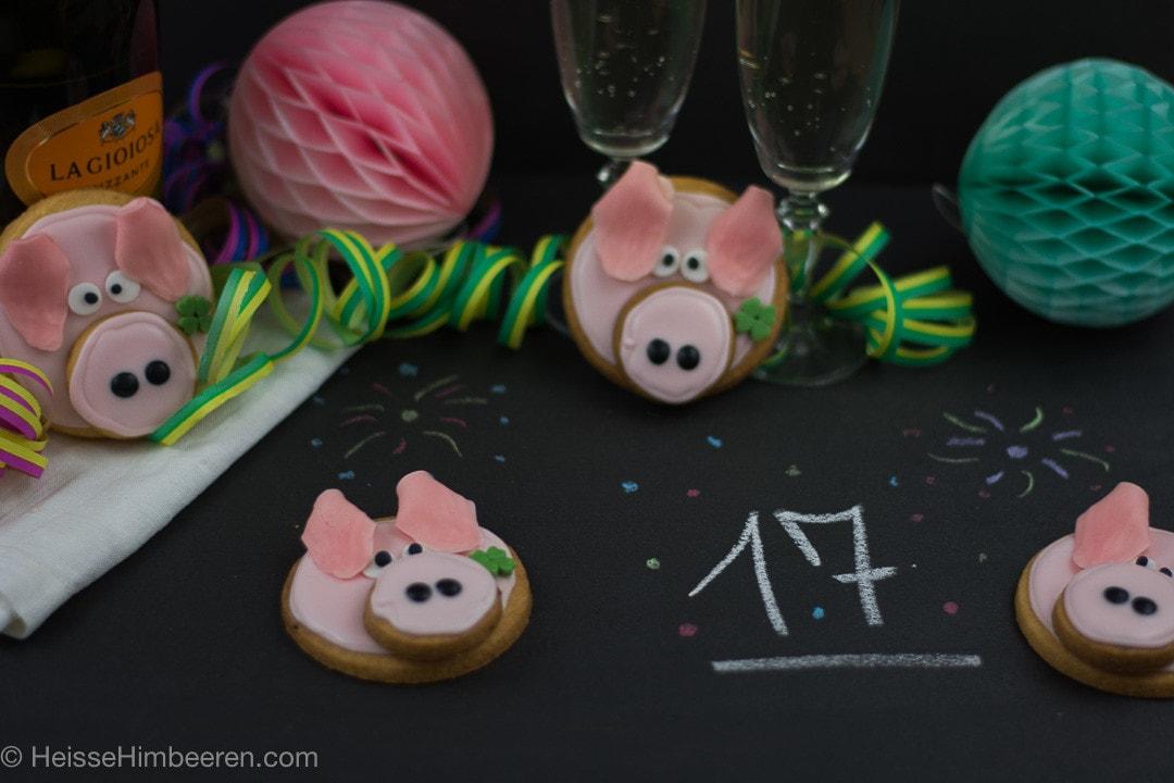 Mehrere Glücksschweinchen aus Mürbeteig auf einem Tisch mit Sekt