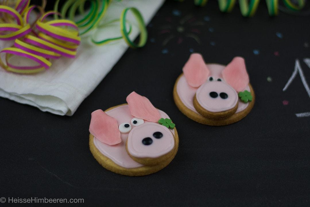 Zwei Glücksschweinchen neben Luftschlangen