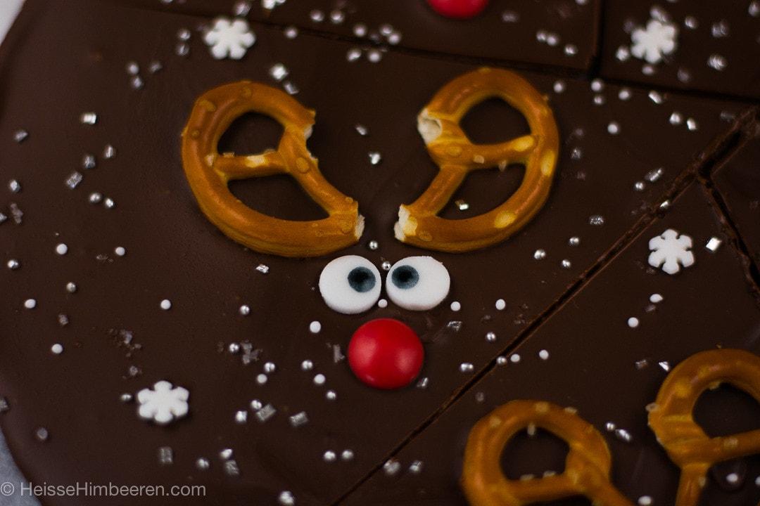 Ein Rentier auf der Schokolade. Man sieht ein Geweih aus einer Brezel, zwei Augen und eine rote Nase