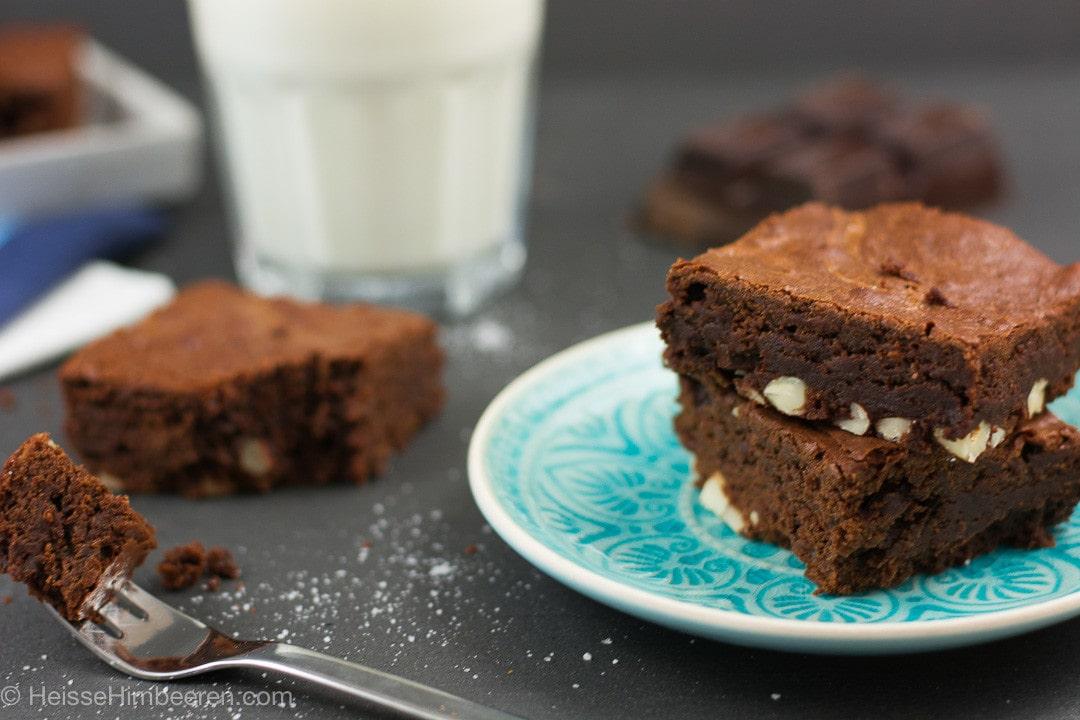 Eine Gabel mit einem Stück Brownie. Im Hintergrund steht ein Glas Milch
