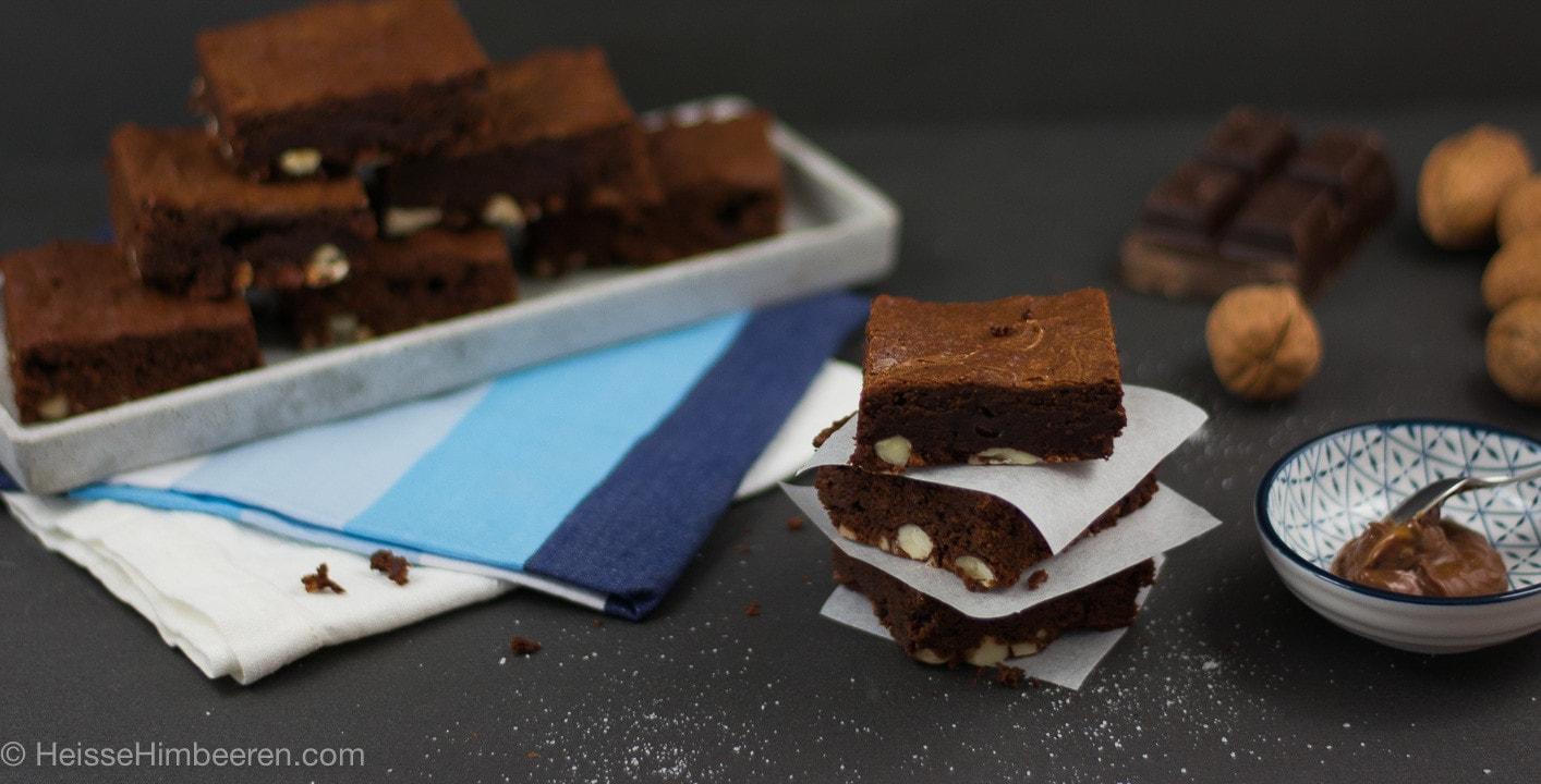 Drei gestapelte Brownies. Im Hintergrund befinden sich viele Brownies auf einem länglichen Teller