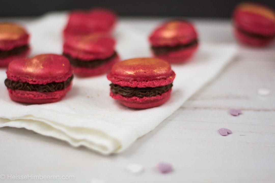 Viele rote Herz Macarons auf einer Serviette. Die Macarons sind mit Gold bestäubt
