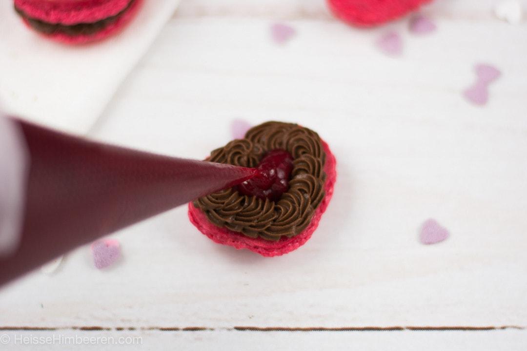 In ein Herz Macaron wird Marmelade mit einem Spritzbeutel eingefüllt