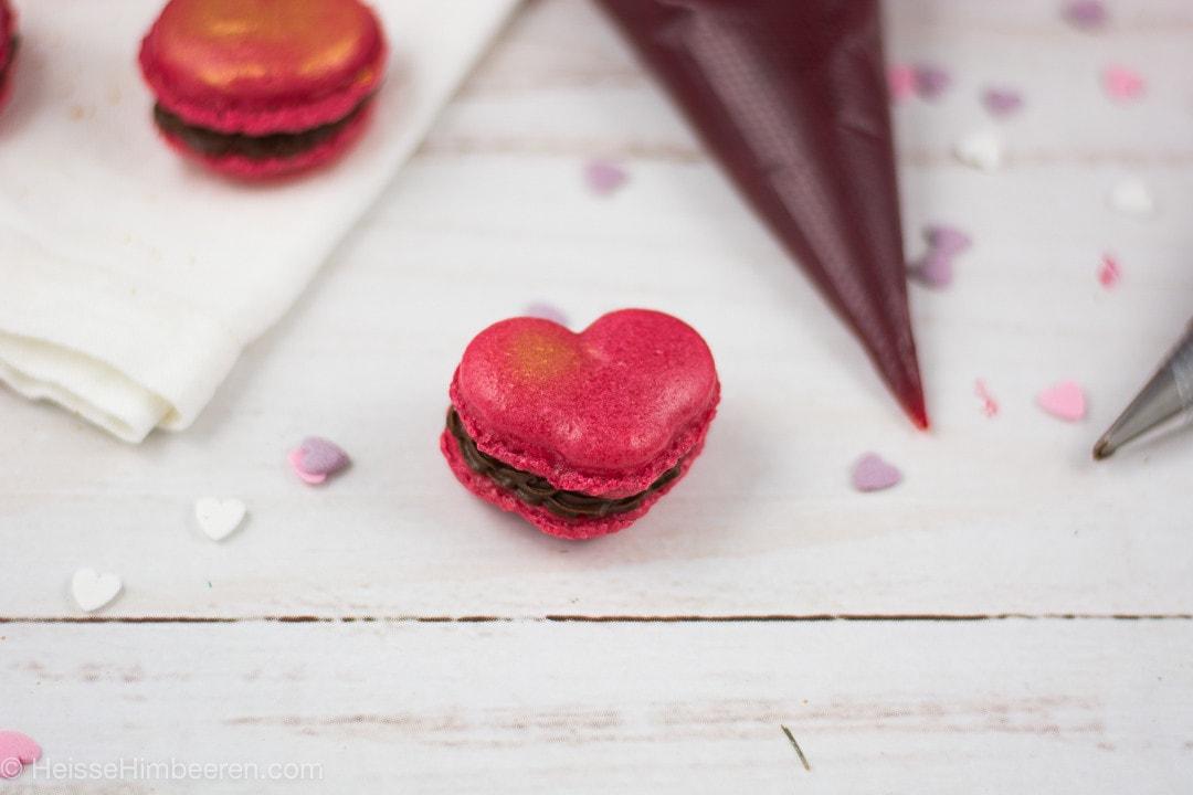 Herz Macarons mit einem Spritzbeutel an der Seite