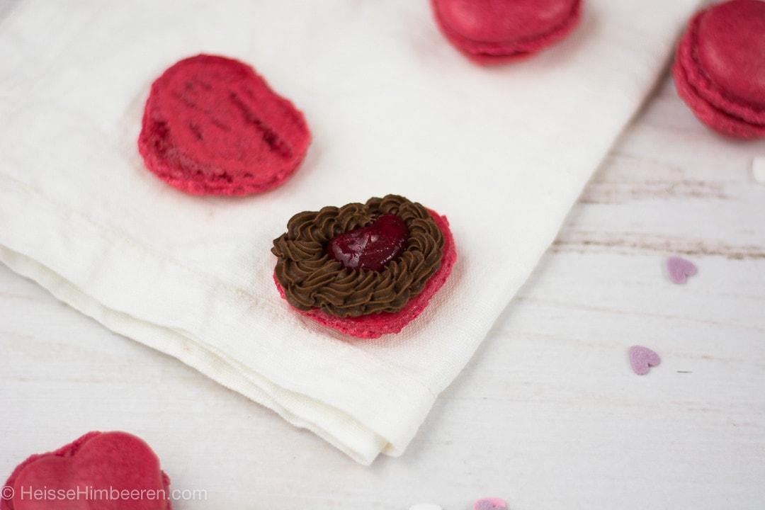 Ein Herz Macaron geöffnet. Man sieht eine Schokoladencreme und in der Mitte ein Herz aus roter Marmelade