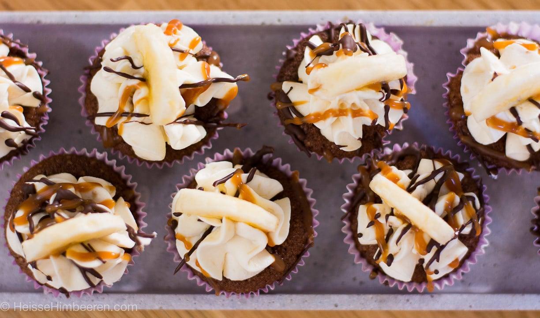Schoko Bananen Cupcakes von oben. Sie sind verziert mit Karamell, Schokolade und einem Bananenstück