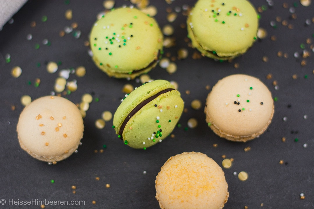 Viele grüne und beige St Patricks Day Macarons auf einem schwarzen Tisch