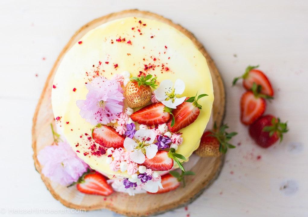 Ein Erdbeerkuchen mit Mascarpone von oben. Man sieht weiße Schokolade, Erdbeeren und Blumen auf dem Kuchen