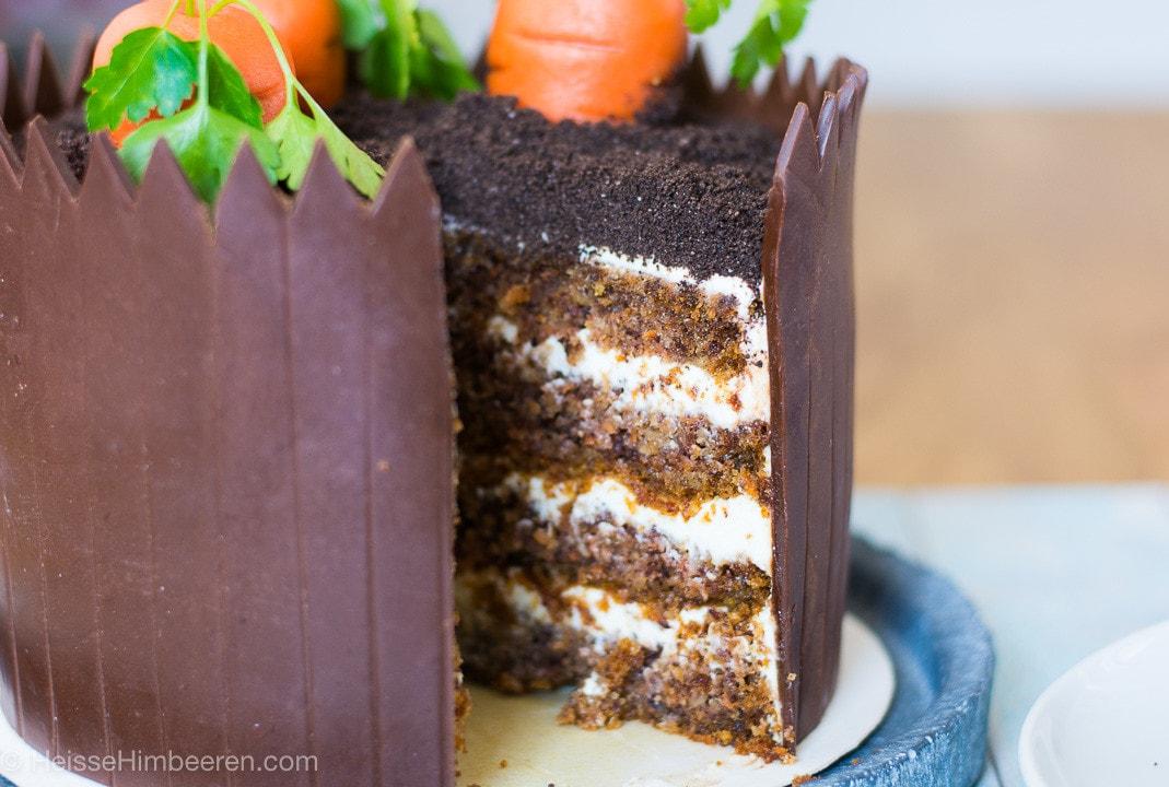 Eine angeschnittene Karottentorte. Man sieht die Creme in der Torte und das Schokoladenbeet