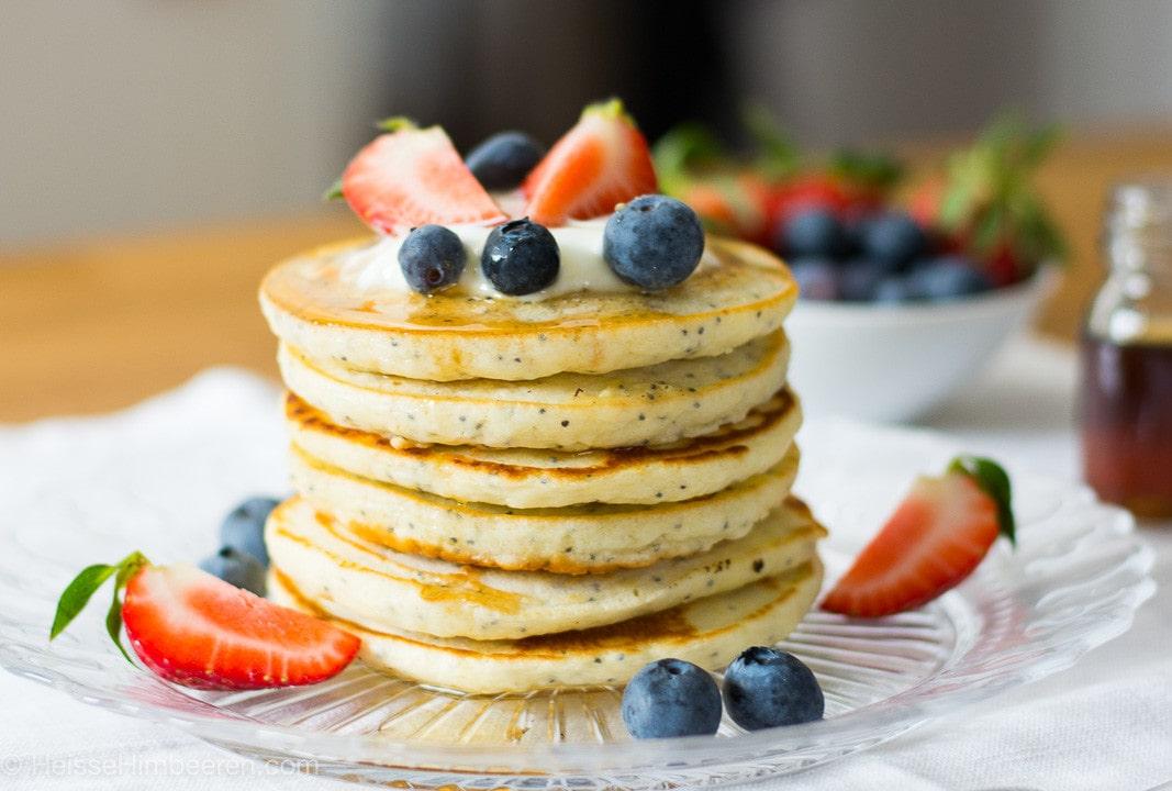 Zitronen Pancakes gestapelt auf einem teller mit Erdbeeren und Blaubeeren und Joghurt