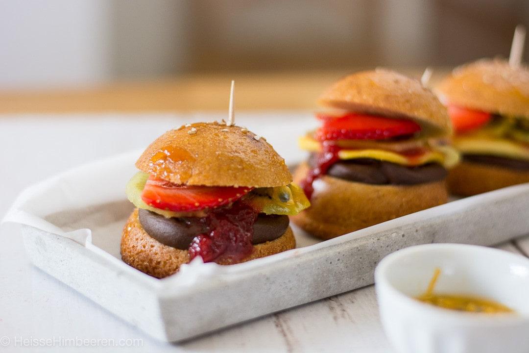Drei süße Burger auf einem länglichen Teller