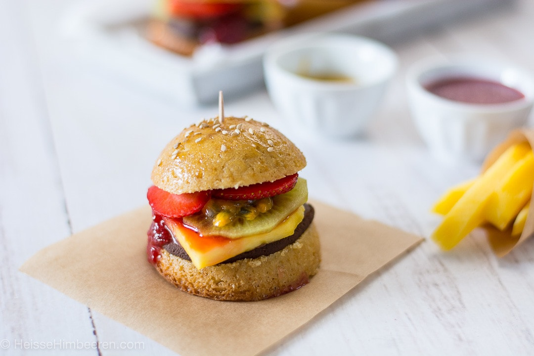 Ein süßer Burger auf einem Backpapier. Im Hintergrund sind Pommes aus Mango
