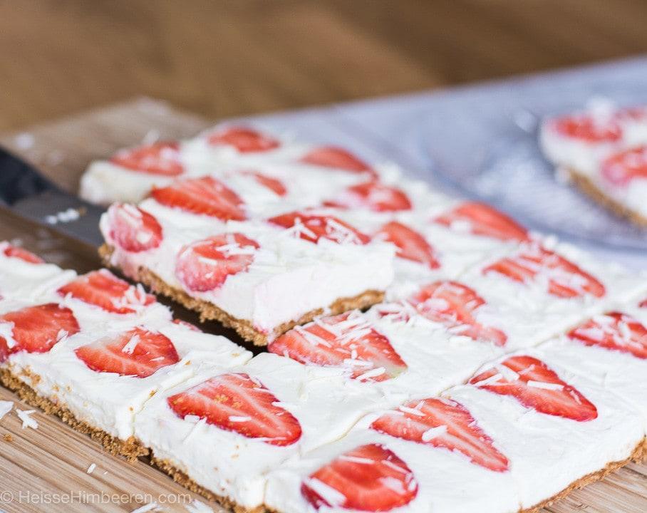 Ein Stück Erdbeer Cheesecake wird hochgehoben
