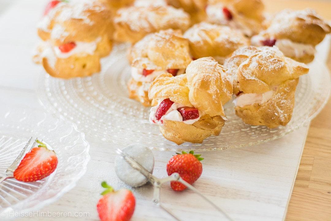 Windbeutel mit Erdbeeren und Sahne. Davor liegen drei Erdbeeren als Dekoration
