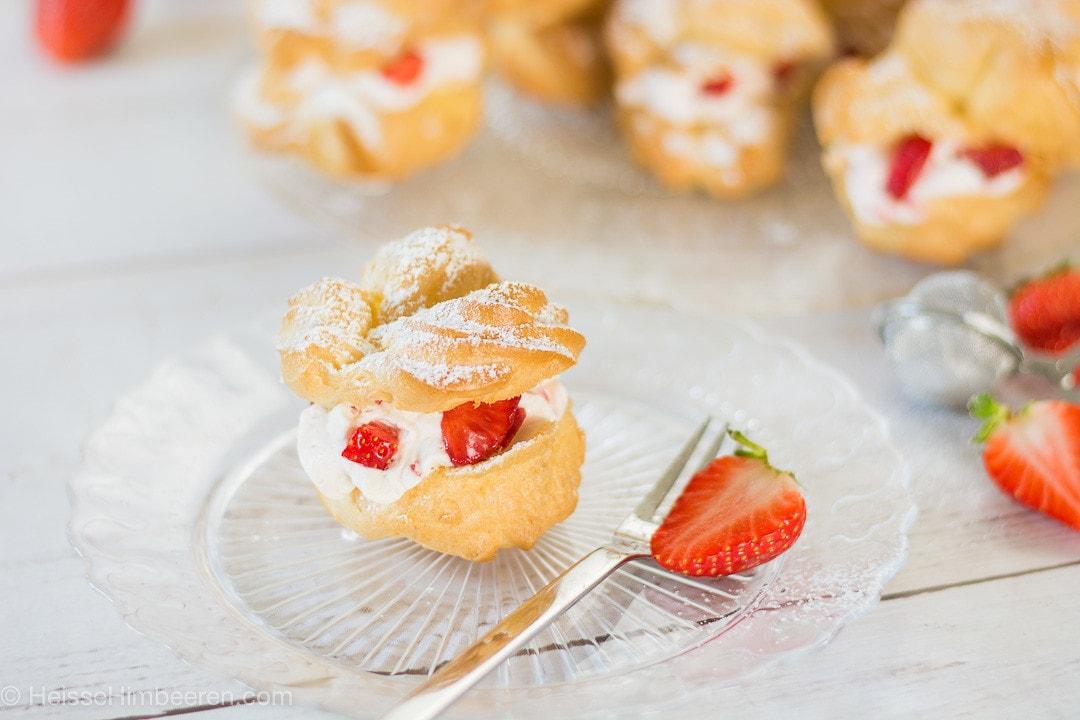 Ein Windbeutel mit Erdbeeren auf einem durchsichtigen Teller
