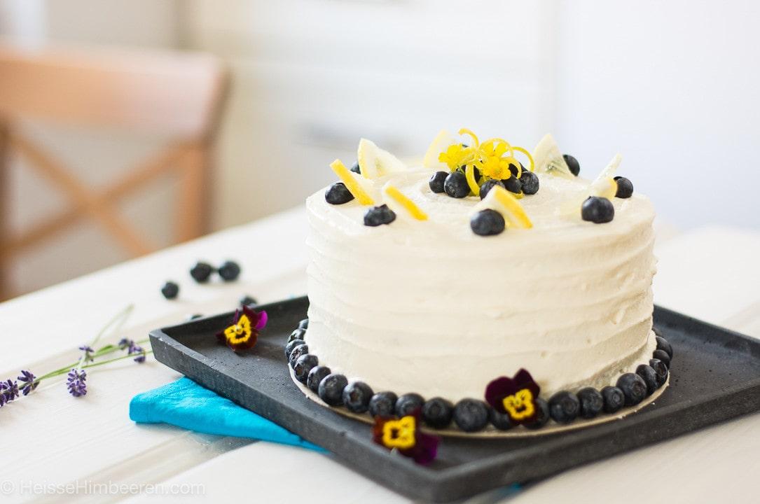 Eine Zitronen Blaubeer Torte auf einer schwarzen Schieferplatte