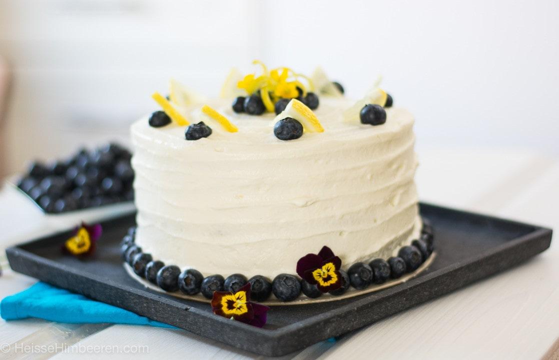 Die Zitronen Blaubeer Torte auf einer Platte. Die Torte ist außenrum mit Blaubeeren dekoriert