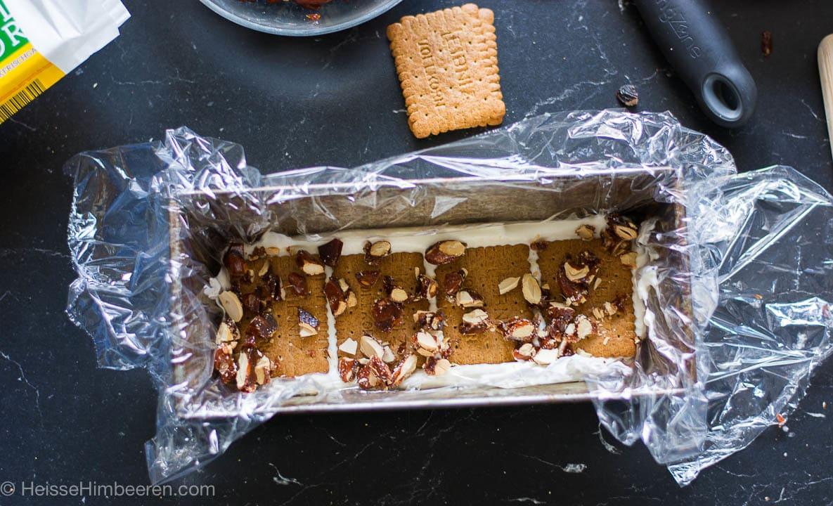 Die Eistorte in der Zubereitung. Nüsse liegen auf Keksen in einer Form