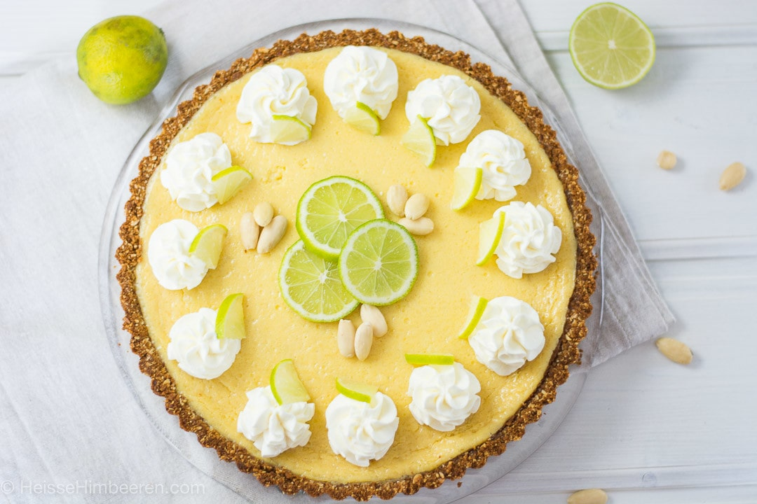 Ein Limettenkuchen von oben. Er ist sehr gelb und mit grünen Limetten dekoriert