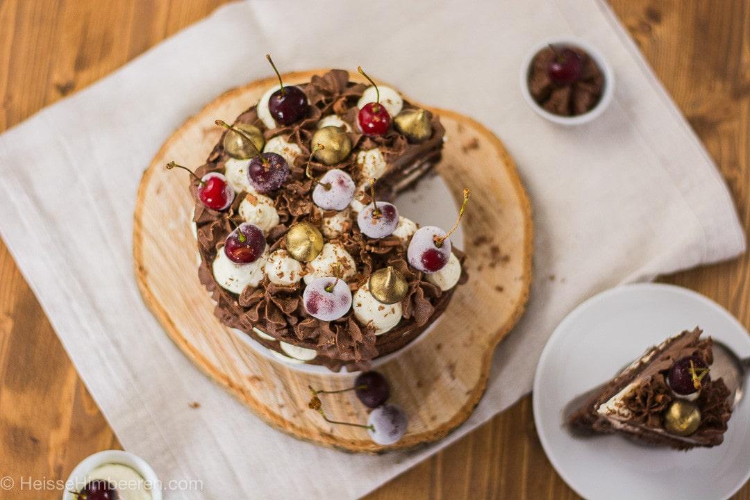 Ein angeschnittener Schoko Kirsch Kuchen mit einem Stück auf einem Teller der daneben steht