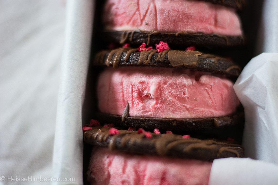 Ein Sandwich Eis mit Schokolade in der Nahaufnahme. Der Fokus geht auf das Erdbeereis