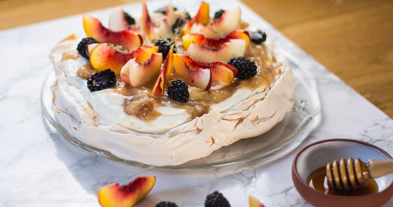 Eine Pavlova mit Brombeeren und frischen Nektarinen auf einem Teller