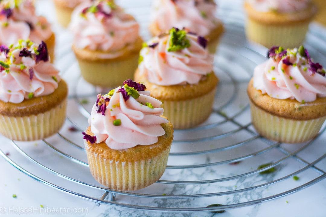 Rosen Cupcakes aus der Nähe. Man erkennt Pistazien auf den Cupcakes